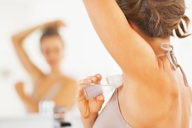 Woman putting on deodorant